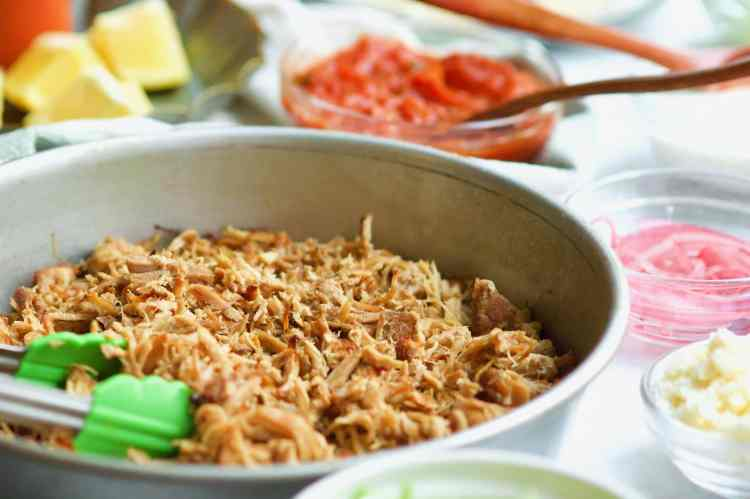 Crispy carnitas served up in a round cake pan, surrounded by lots of other small bowls filled with taco toppings.