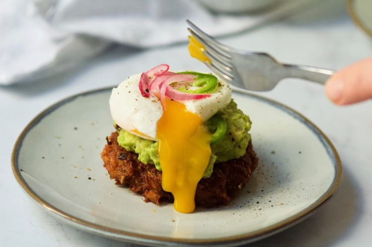 A poached egg sits on top of a potato pancake topped with guacamole. The side has been pierced with the edge of a fork sending molten yolk spilling down the side. The fork has just been pulled away from the egg, a bit of yolk clinging to the tines.