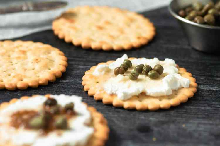 a close up shot of a cracker spread with goat cheese and topped with capers. other crackers are out of focus around it.