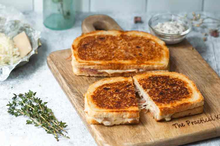 Two golden brown grilled cheese sandwiches on a wooden cutting board. The one in front has been sliced in half and gooey strings of cheese are stretched between the two halves.