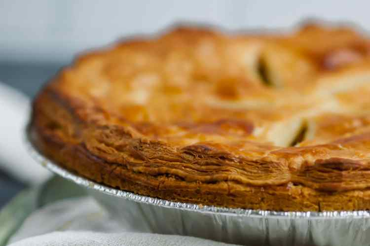 A close up of the flaky layers of the inch-tall puff pastry top of the samosa pot pie.