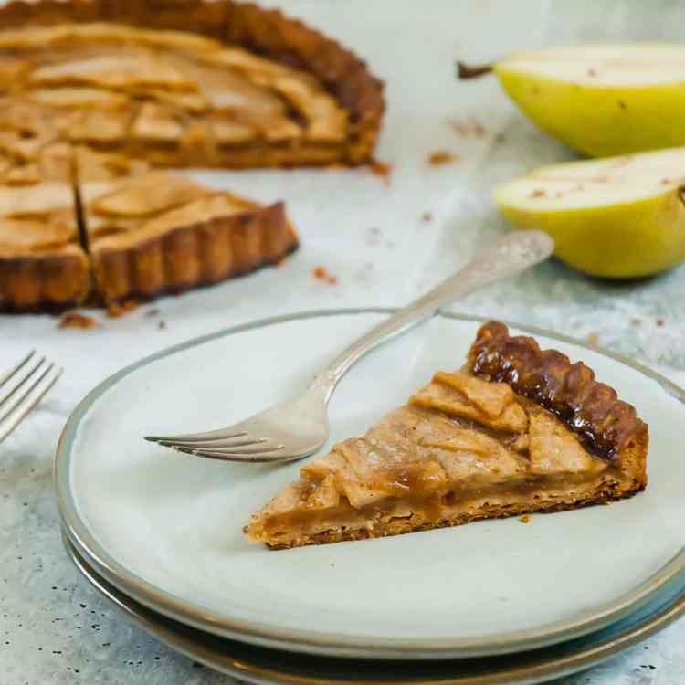 a small slice of pear and gruyere tart sits on a small grey plate with a fork. the rest of the tart is slightly out of focus in the background along with two halves of a pear.