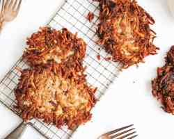 an overhead shot of potato pancakes on a narrow wire cooling rack. two are stacked on top of each other, one sits alone. another is cropped just out of frame.