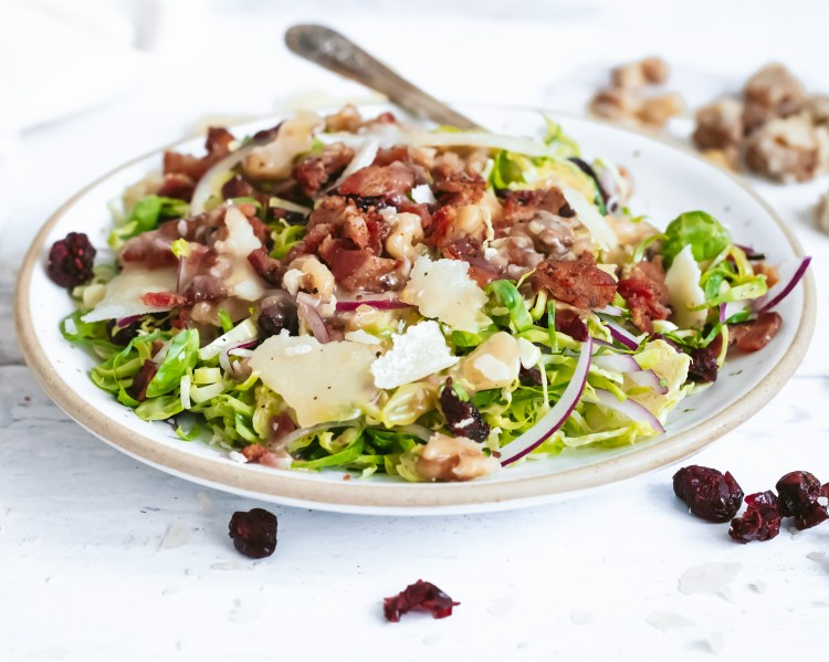 a side view of a shaved brussels sprouts salad with maple bacon vinaigrette