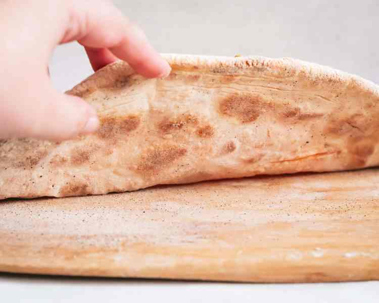 A hand picks up the edge of a pizza showing the crispy, leopard spotted bottom hot off the baking steel.