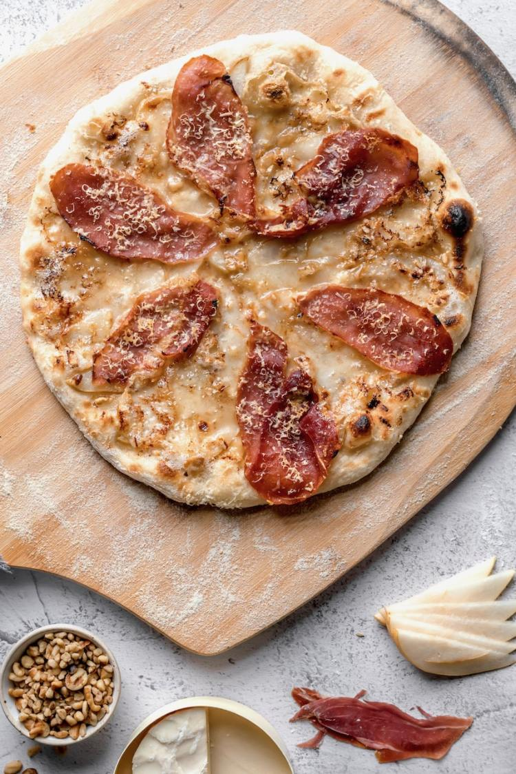 charcuterie board pizza on a wooden pizza peel