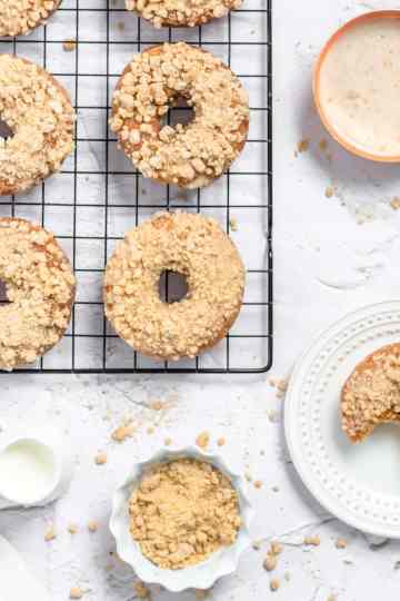 an overhead shot of crumb cake doughnuts on a cooling rack with a bowl of crumbs nearby