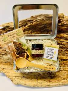 a metal tin box with a wooden spoon, mulled wine spices, soap, and chef's burn balm