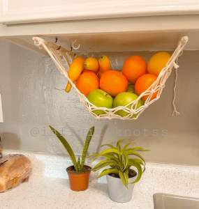 a hanging macrame fruit hammock that fits under cupboards