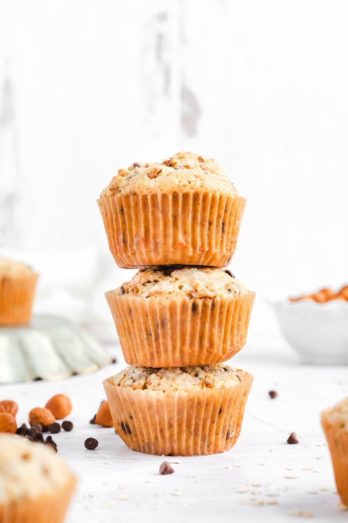 a stack of three muffins. hazelnuts and mini chocolate chips are on the counter around it.