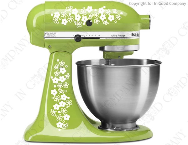 a green kitchenaid mixer with white floral pyrex-style designs on the side