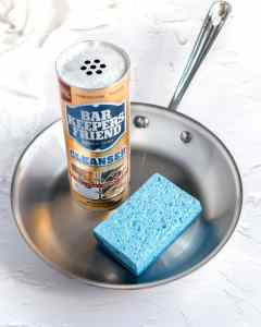 a can of bar keeper's friend and a blue sponge sit in the middle of a shiny 8 inch fry pan
