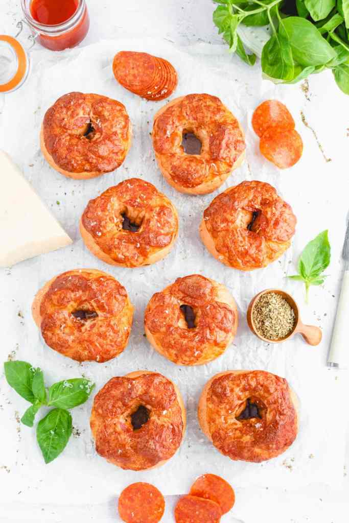 an overhead shot of 8 pizza bagels surrounded by basil, parmesan, and tomato sauce