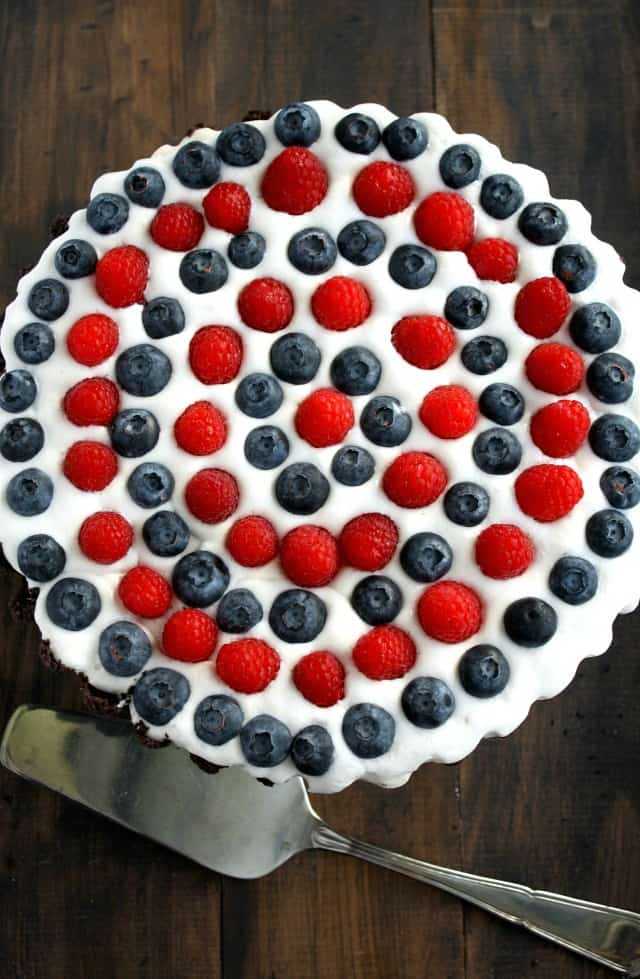 Pretty red and blue berries sit on top of a creamy filling and an Oreo cookie crust. A no-bake patriotic dessert! #july4th #patriotic #nobake