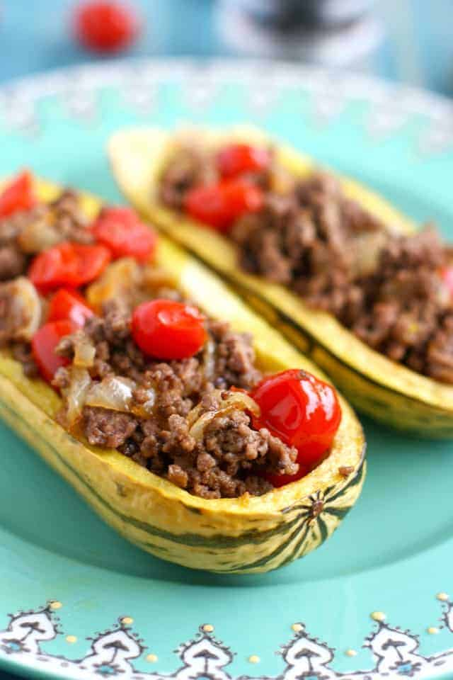 Delicata squash stuffed with ground turkey, tomatoes, and onions. An easy, healthy meal. Whole 30 compliant.