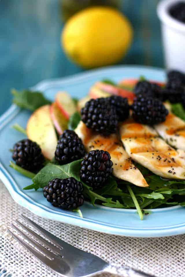 A fresh green salad topped with blackberries, apples, chicken, and a lemon poppy seed dressing. So delicious for spring! #ad