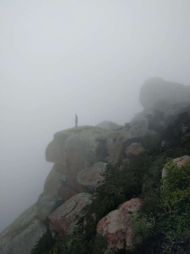 One person stood on a clifftop on a foggy day.