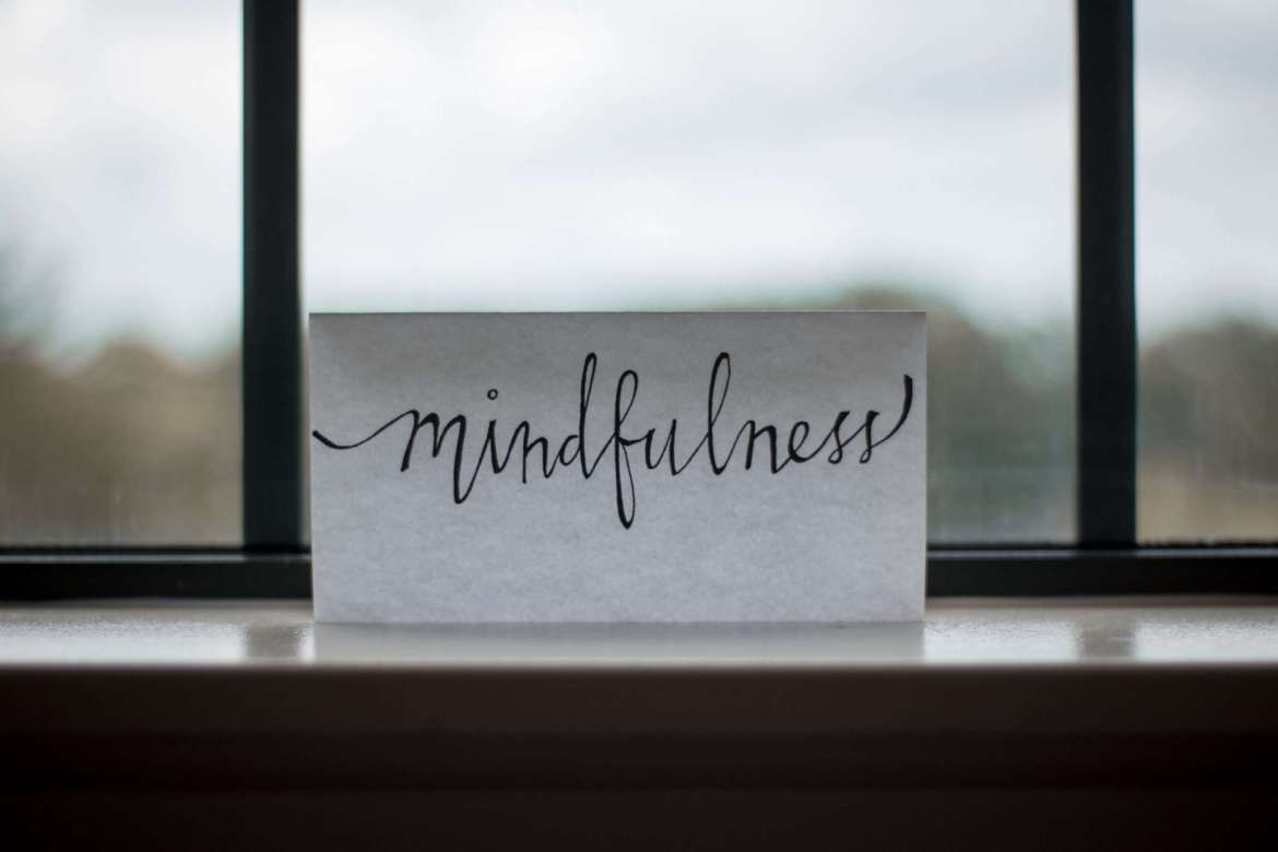 In front of a window is a single piece of paper. The paper is stood up and has mindfulness written on it