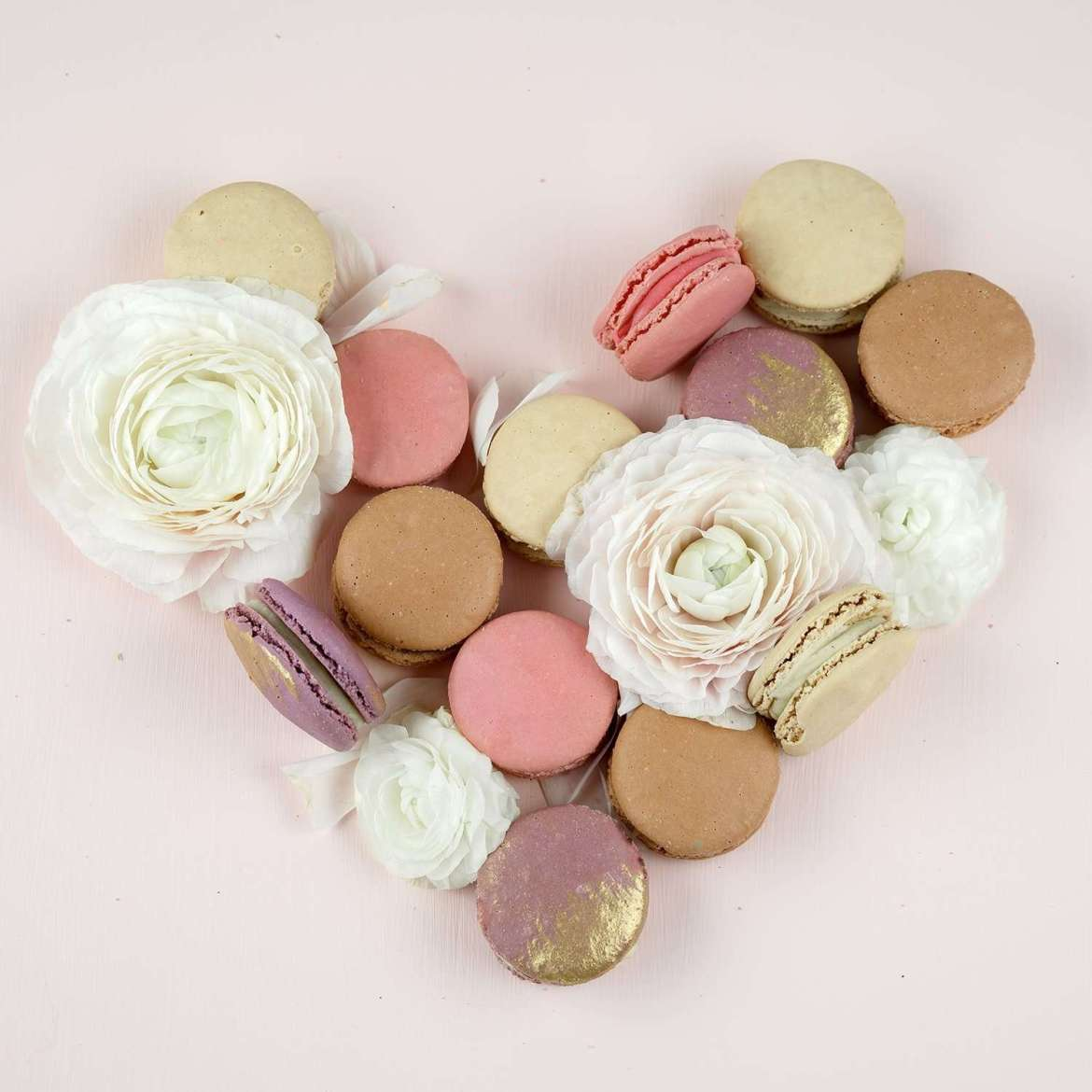 A pale pink background. White flowers and pink, brown, purple and white macarons are making a heart
