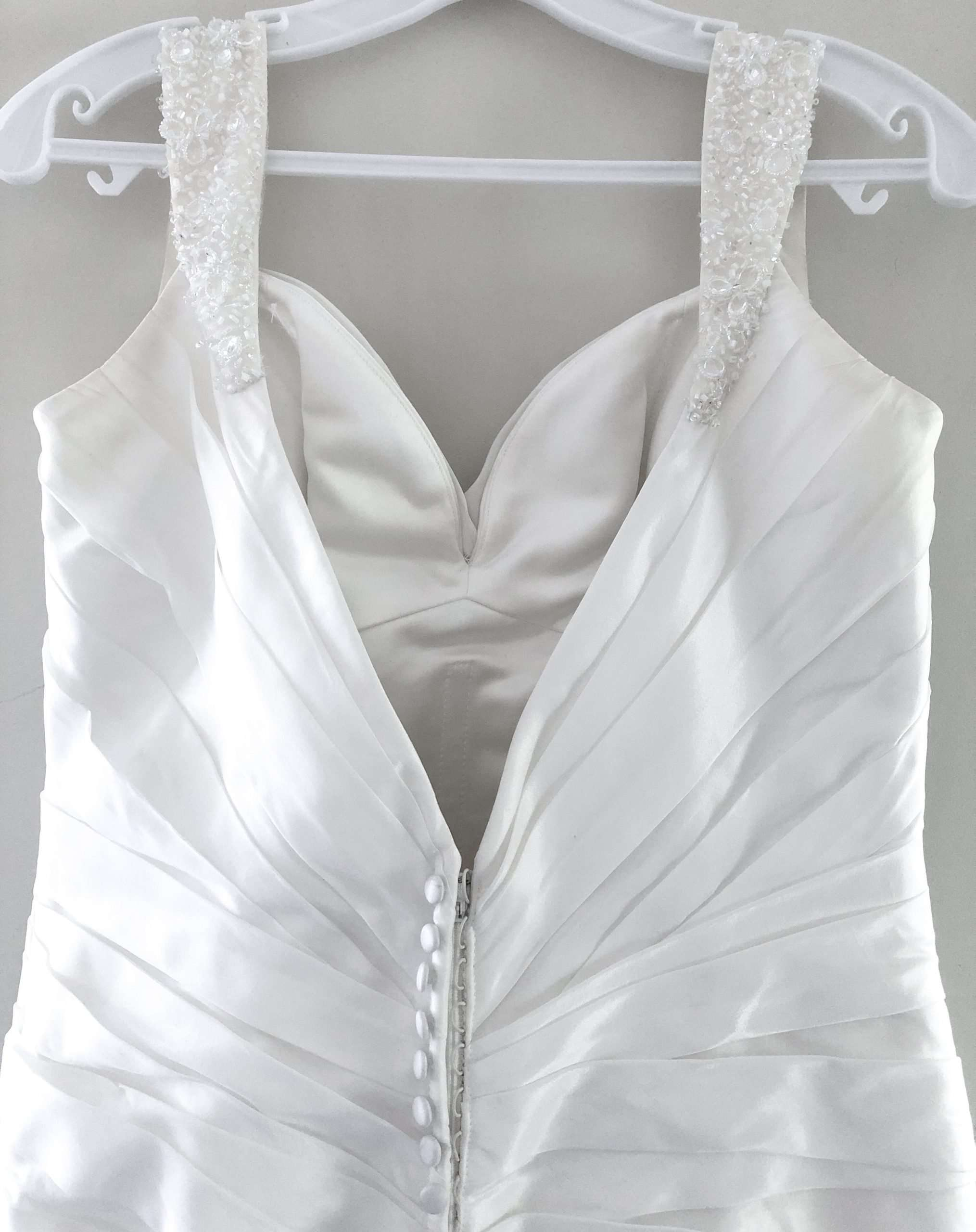 The back of Lisa's wedding dress on the hander. The dress has sparkly straps and is low cut at the back