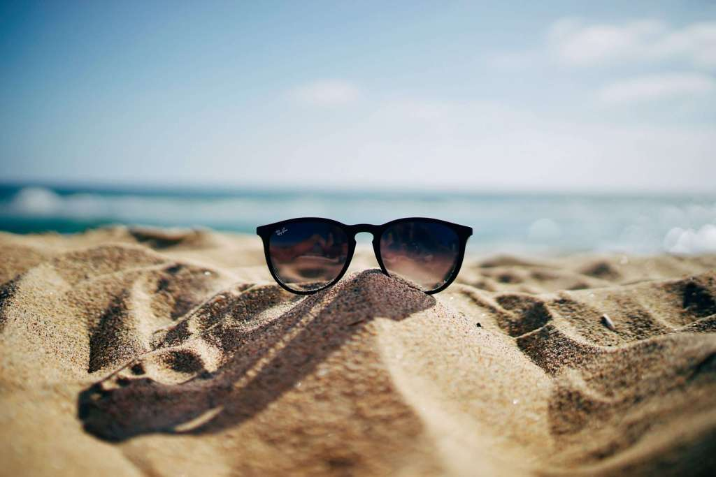 A pair of black sunglasses is resting on a very small sand hill. The blue sea and sky are in the background