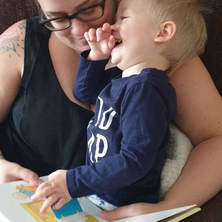 Lisa and Little J are sat on the sofa. Lisa is reading a book to little J and he is laughing