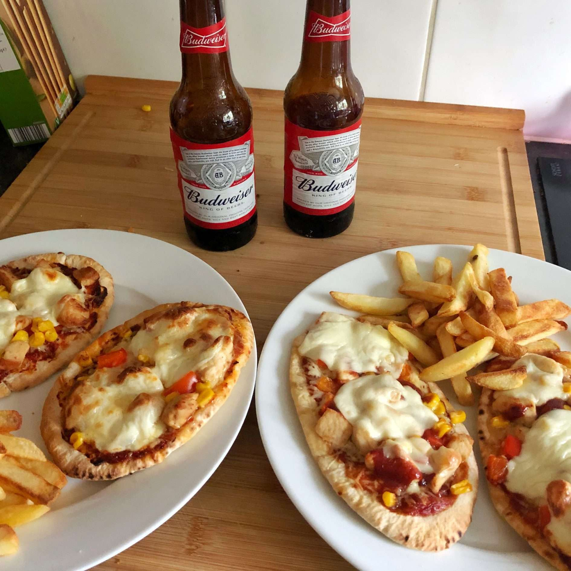 Homemade pizza, with chips, is on white plates. They are sat on a wooden chopping board and there are two bottles of Budweiser