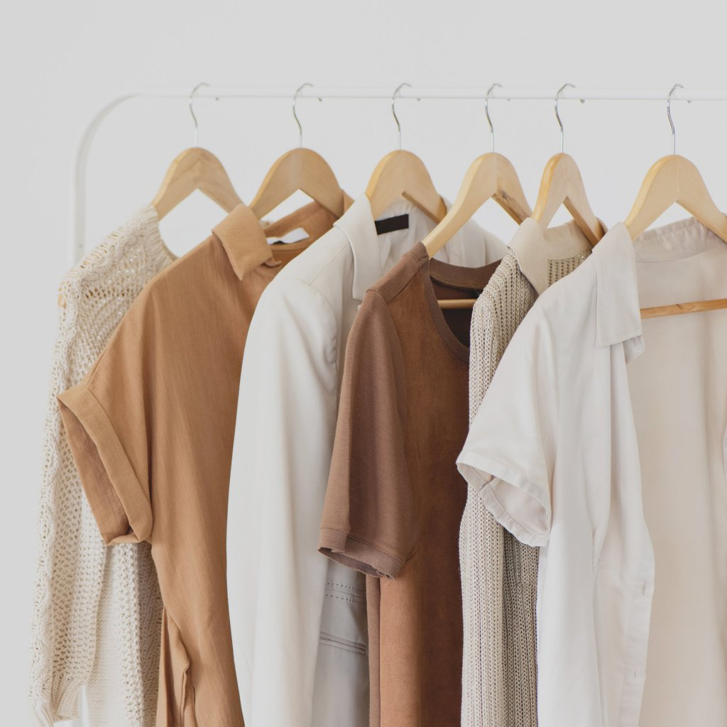 T-shirts, shirts and jumpers in soft browns and beiges are hung up neatly on a rail
