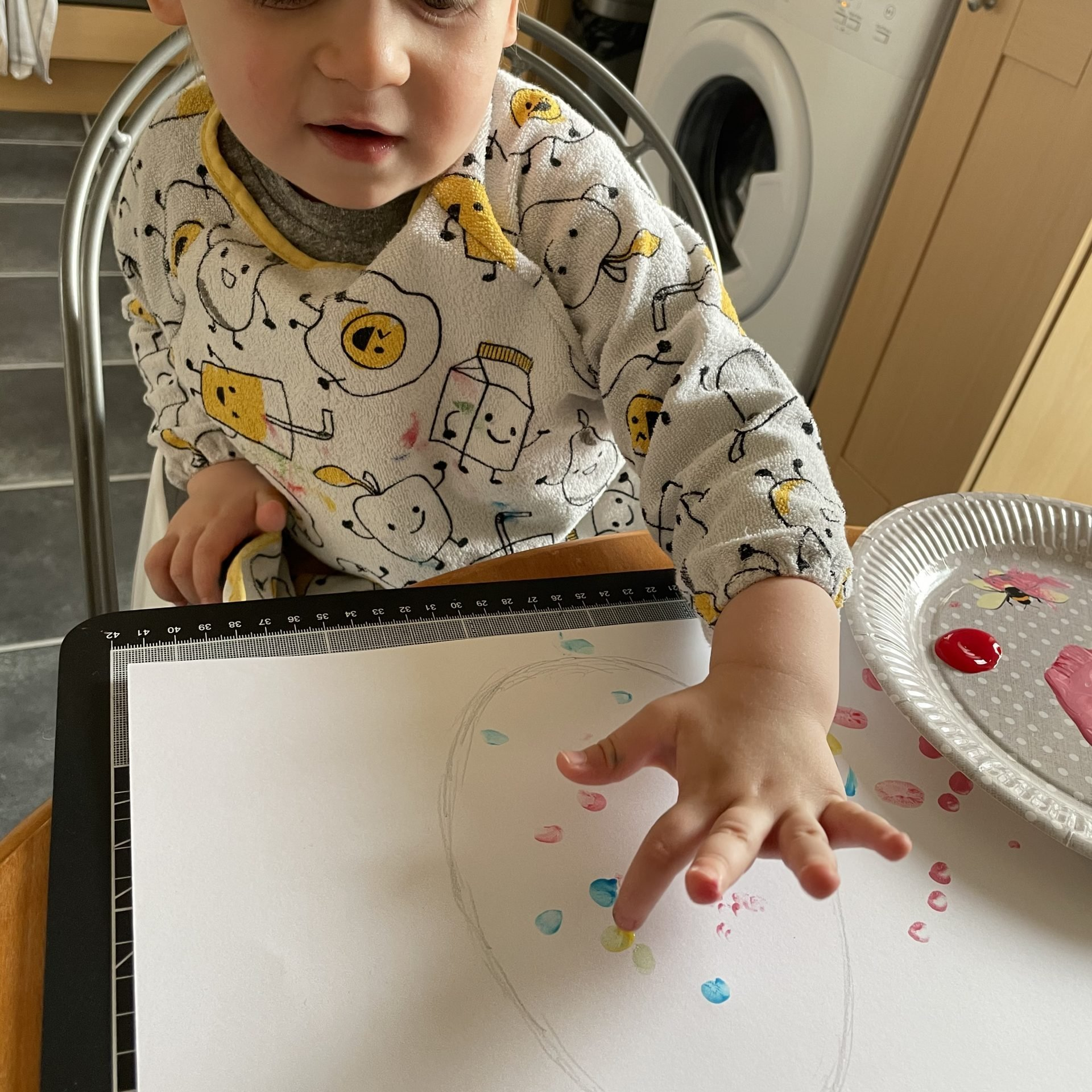 Little J is sat at the table wearing a yellow and white apron/cover. He is using his fingers to paint a picture of an easter egg