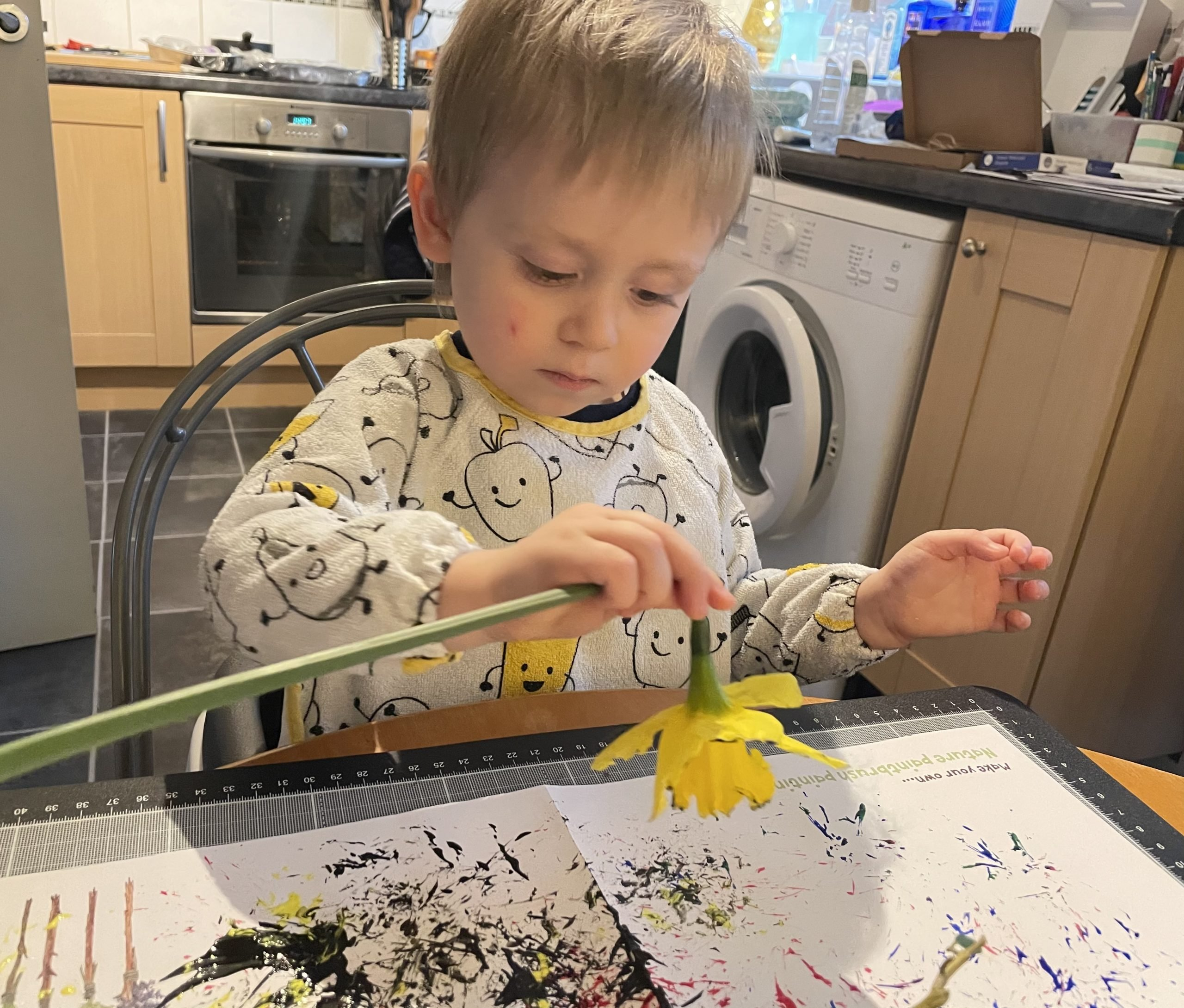 On a wooden table is a large sheet of white paper with paint splatters all over it. Little J is using the nature paintbrushes to paint. The nature paintbrush is made out of a daffodil