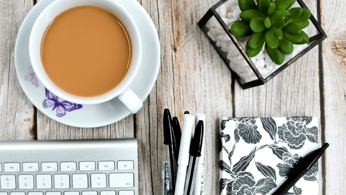 On a wooden table is a white cup and saucer with a purple butterfly on the saucer. The cup has a strong cup of tea in it. Also on the table is the edge of a computer keyboard, black and white pens, a black and white notebook and a Succulent plant in a pot with white pebbles