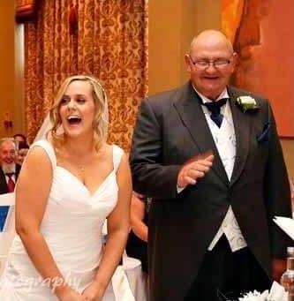 Lisa and Ian on Lisa's wedding day. Lisa is in a white wedding dress and Ian is in a suit. They are both laughing at something Ian had said
