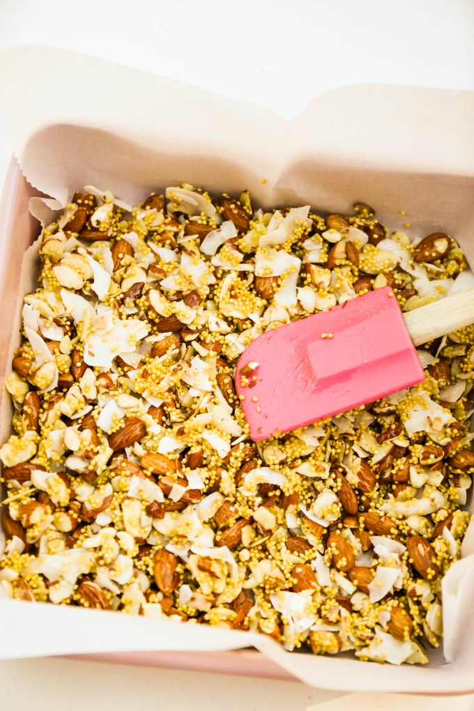 granola bar ingredients spread in baking pan with pink spatula