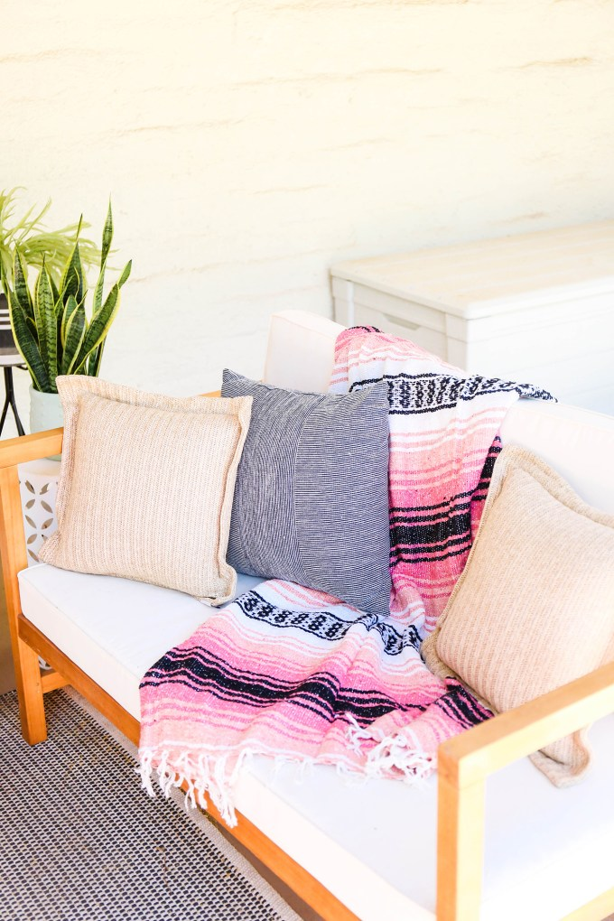 striped mexican serape blanket rests on modern white outdoor loveseat