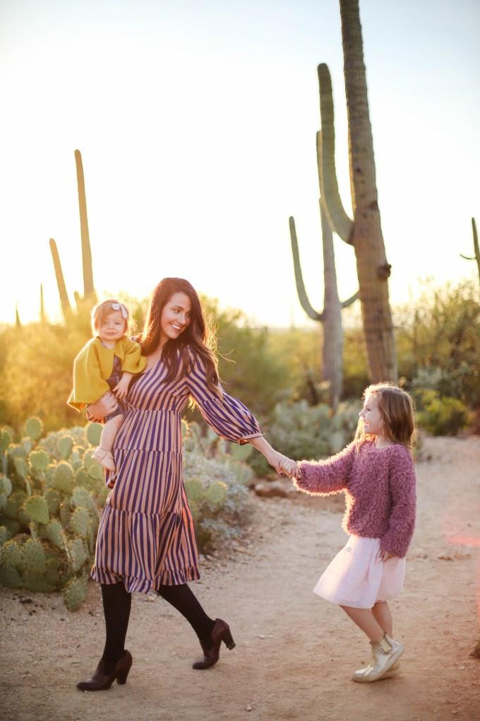 mom and daughters walk in desert