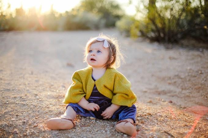 baby girl sitting in sand in desert at sunset