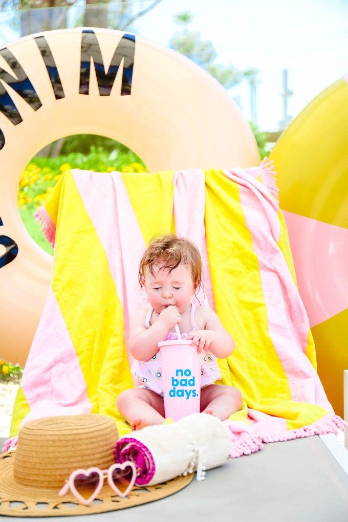 baby girl sipping through a straw in front of colorful towels and pool floats