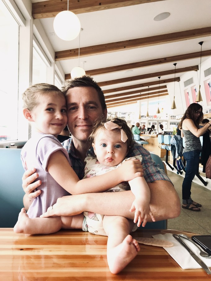 dad posing in diner with daughters