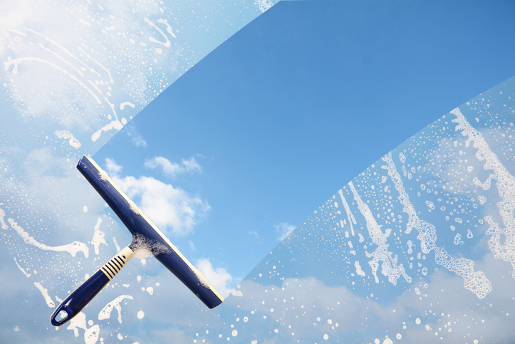 Rubber squeegee cleans a soaped window and clears a stripe of blue sky with clouds, concept for tranparency or spring cleaning, copy space in the background