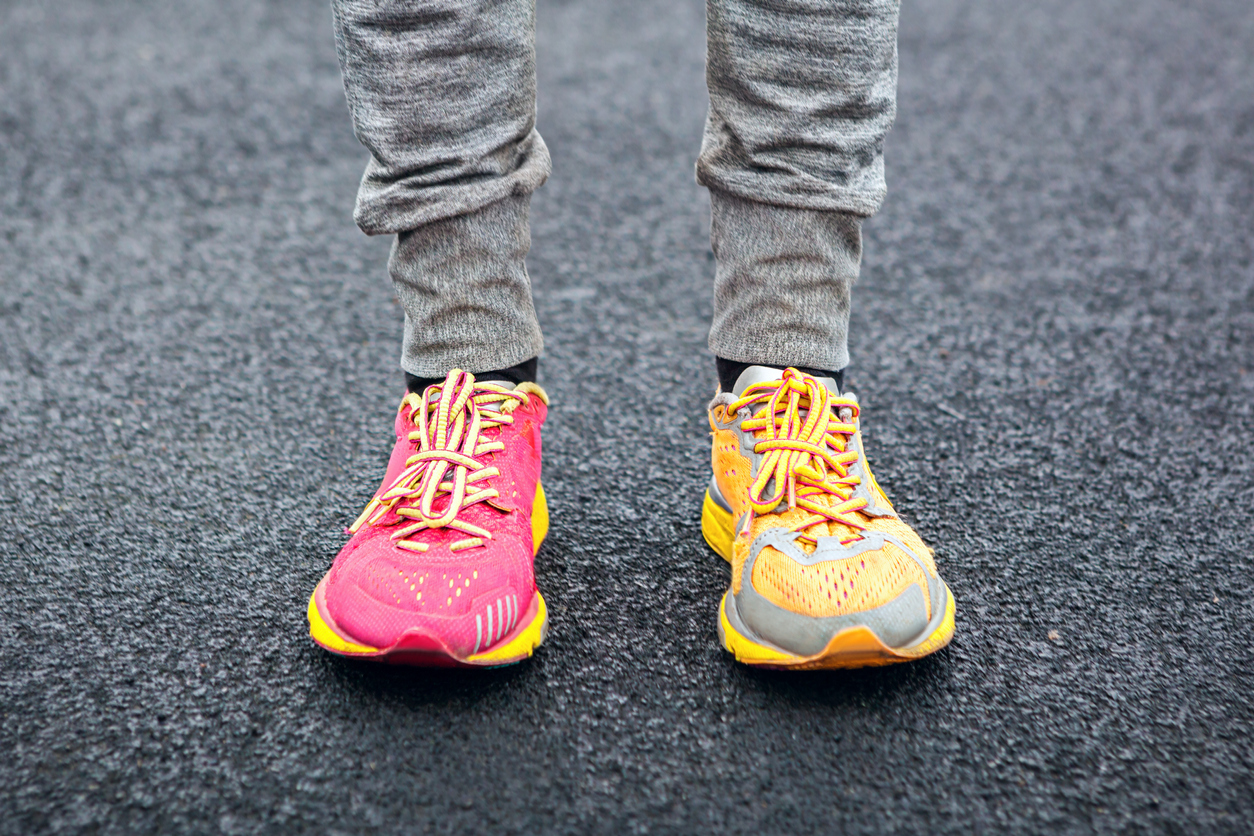 Legs in multi-colored running shoes.