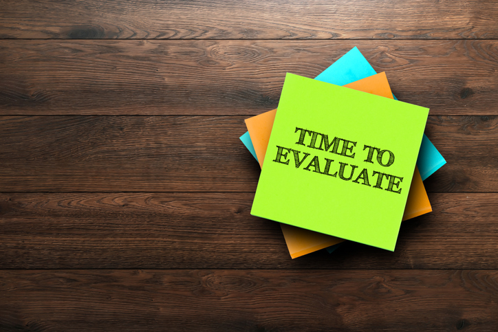 Time To Evaluate, the phrase is written on multi-colored stickers, on a brown wooden background. Business concept, strategy, plan, planning.