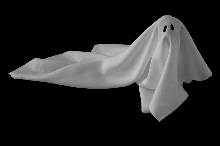 White ghost sheet costume rise up from the floor with black background.