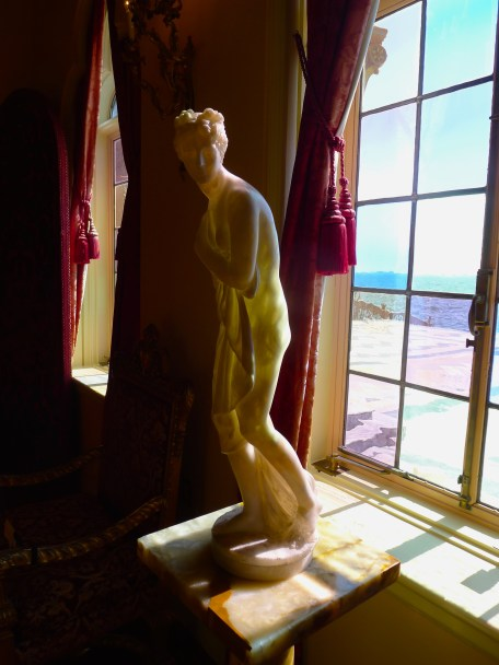 Alabastor statue catches the light through the antique colored glass of Ca' d'Zan