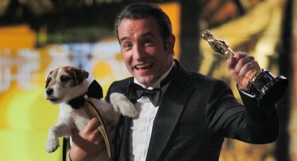 """Best actor winner Dujardin of France carries Uggie the dog after """"The Artist"""" wins the Oscar for Best Picture at the 84th Academy Awards in Hollywood"""