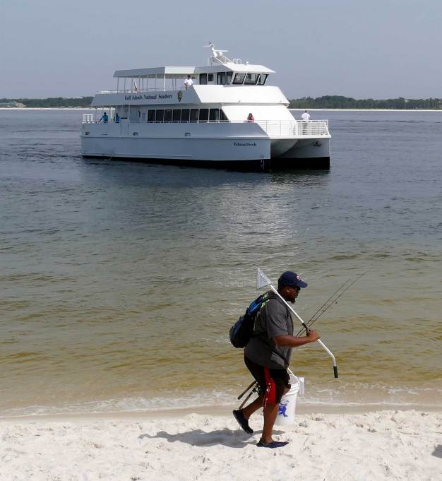 A fisherman walks near Fort Pickens as one of Pensacola's new ferry boats sits behind him in the bay. (Bruce Graner/The Pulse)