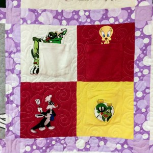 A collection of Loonie Tunes characters embroderied on pockets are combined to make one block in a child's t-shirt quilt