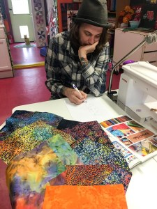 Jake is sketching out a quilting design with fabric swatches next to him