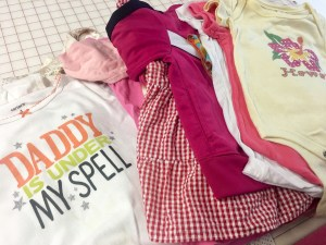 A pile of baby clothes waiting to be made into a childhood memory quilt by The Quilt Rambler