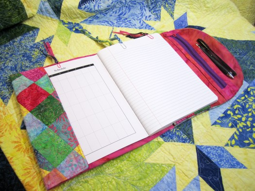 Scrap pieced notebook cover is open to show the pages of the notebook and zippered pen pouch