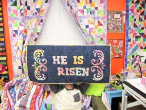 "Man holding up appliquéd quilt saying ""He is Risen"""